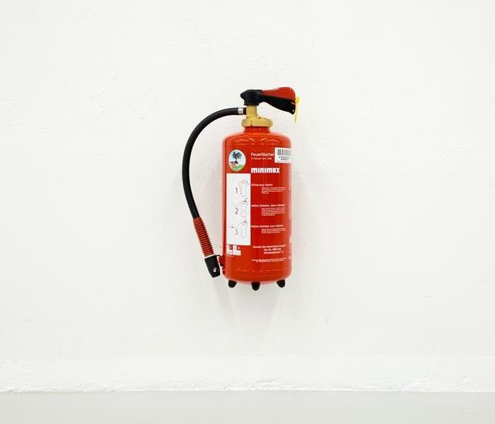 A Bright Red Fire Extinguisher Mounted On A White Wall